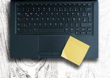关于膝上型计算机键盘的黄色稠粘的笔记反对白色木桌 免版税库存图片