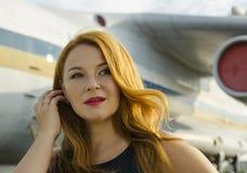 关于航空器的可爱的红头发人妇女在愉快旅行之外 库存照片