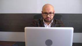 关于计算机的办公室工作者键入的报告 研究便携式计算机的商人在办公室 股票录像