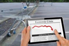 关于金融危机读书的新闻用在计算机片剂的手 免版税库存图片