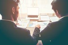 关于销售报告图的商人讨论与在木桌上的白色屏幕膝上型计算机 库存图片