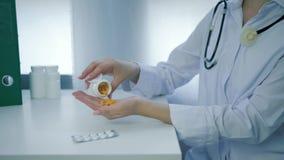 关于食物和健康福利的专家打开瓶子维生素并且倾吐黄色圆的药片入在白色桌上的棕榈 股票录像