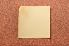关于黄柏板背景的黄色稠粘的岗位笔记 免版税库存照片