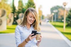 读关于财务新闻的确信的妇女信息,当走在公司走廊在工休期间时 库存照片