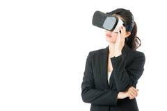 关于VR耳机玻璃设备的亚洲女商人问题 库存图片