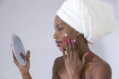 关心她皮肤采取 在她的面孔的毛巾传播的奶油包裹的美丽的年轻美国黑人的妇女画象  库存图片