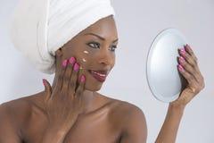 关心她皮肤采取 在她的面孔的毛巾传播的奶油包裹的美丽的年轻美国黑人的妇女画象  免版税库存图片