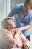 关心对不适的妇女的男性护士 免版税库存图片
