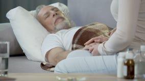 关心对不适的父亲的女儿在床、退休和疾病,健康上 股票视频