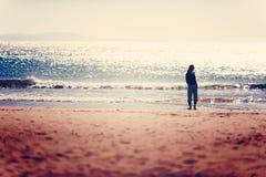 关心散步在索维拉海滩的日落前的自由的妇女 库存图片