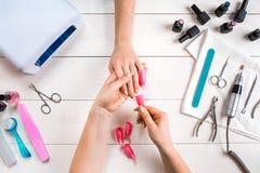 关心棉花取消拖把油漆的指甲盖钉子 归档与专业指甲锉的女性手特写镜头钉子在秀丽钉子沙龙 顶视图 免版税图库摄影
