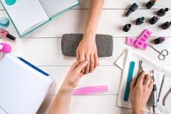 关心棉花取消拖把油漆的指甲盖钉子 归档与专业指甲锉的女性手特写镜头钉子在秀丽钉子沙龙 顶视图 图库摄影