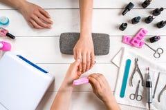 关心棉花取消拖把油漆的指甲盖钉子 归档与专业指甲锉的女性手特写镜头钉子在秀丽钉子沙龙 顶视图 库存照片