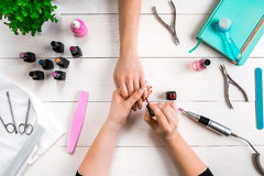 关心棉花取消拖把油漆的指甲盖钉子 归档与专业指甲锉的女性手特写镜头钉子在秀丽钉子沙龙 顶视图 免版税库存照片