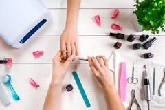 关心棉花取消拖把油漆的指甲盖钉子 归档与专业指甲锉的女性手特写镜头钉子在秀丽钉子沙龙 顶视图 库存图片