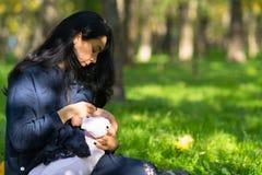 关心的母亲哺乳的婴孩在豪华的城市公园 图库摄影