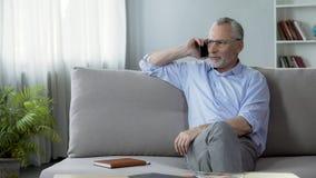 关心的退休的父亲坐沙发和告诉他的孩子,通信 免版税库存照片