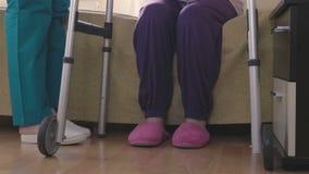 关心辅助教的更老的残疾妇女如何走与步行者 股票录像
