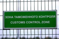 关税控制区域-一个标志用在入口的俄语和英语对车检查点 板材是绿色的在 免版税库存图片