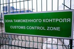 关税控制区域-一个标志用在入口的俄语和英语对车检查点 板材是绿色的在 库存图片