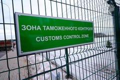 关税控制区域-一个标志用在入口的俄语和英语对车检查点 板材是绿色的在 免版税库存照片