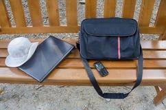 关闭一个便携式计算机、袋子、电话和帽子在长木凳 免版税库存图片