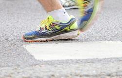 关闭一个公赛跑者的蓝色和黄色鞋子 图库摄影