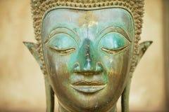 关闭一个古老铜菩萨雕象的面孔在贺尔Phra Keo寺庙外面在万象,老挝 免版税图库摄影