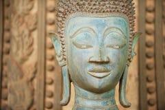 关闭一个古老铜菩萨雕象的面孔在贺尔Phra Keo寺庙外面在万象,老挝 免版税库存图片