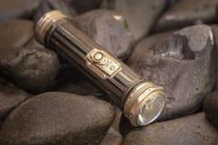 关闭一个古色古香的1920年` s手电的射击在小卵石背景中 免版税库存图片
