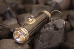 关闭一个古色古香的1920年` s手电的射击在小卵石背景中 库存图片