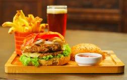 关闭一个可口汉堡包用牛肉、烟肉、葱、蕃茄、莴苣和乳酪与上部面包片与 免版税图库摄影