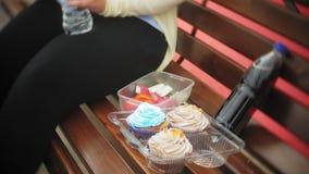 关闭一个可爱的矮小的肥胖女孩,潜水在蛋糕和菜之间,坐长凳在咖啡馆, a的概念 影视素材