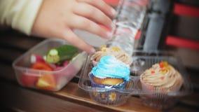 关闭一个可爱的矮小的肥胖女孩,潜水在蛋糕和菜之间,坐长凳在咖啡馆, a的概念 股票录像