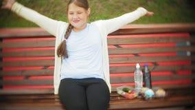 关闭一个可爱的矮小的肥胖女孩,潜水在蛋糕和菜之间,坐长凳在咖啡馆, a的概念 股票视频