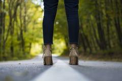 关闭一个女孩的脚在森林公路中间 库存照片