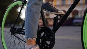 关闭一个女孩的英尺长度起动的牛仔裤和的运动鞋的骑她有绿色轮子的迁徙的自行车,推挤 影视素材