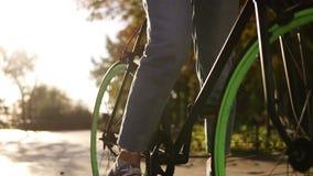 关闭一个女孩的英尺长度起动的牛仔裤和的运动鞋的骑她有绿色轮子的迁徙的自行车,推挤 股票视频
