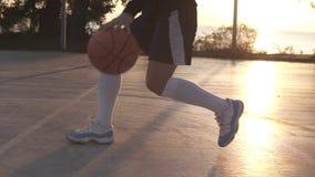 关闭一个女运动员腿的英尺长度在白色高尔夫球袜子和运动鞋的 女性baasketball球员弹跳球从 股票录像