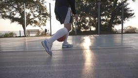 关闭一个女运动员腿的英尺长度在白色高尔夫球袜子和运动鞋的 女性baasketball球员弹跳球从 股票视频