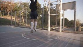 关闭一个女运动员腿的英尺长度在白色高尔夫球袜子和运动鞋的 女性baasketball球员弹跳球从 影视素材