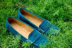 关闭一个对绿松石妇女在草的` s鞋子 免版税库存图片