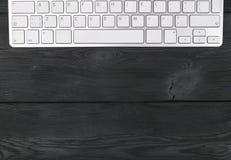 关闭一个工作场所的看法有无线键盘的,在老黑木桌背景的钥匙 免版税图库摄影