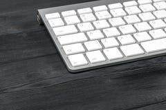 关闭一个工作场所的看法有无线键盘的,在老黑木桌背景的钥匙 免版税库存图片