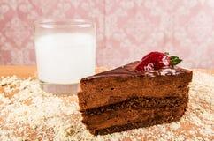 关闭一个巧克力蛋糕用在上面的一个草莓,与一杯牛奶,在一张桌里有桃红色背景 免版税库存照片
