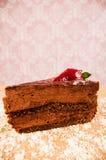 关闭一个巧克力蛋糕用在上面的一个草莓,在一张桌里有桃红色背景 免版税图库摄影