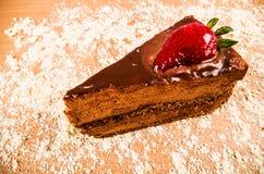 关闭一个巧克力蛋糕用在上面的一个草莓,在一张桌里有桃红色背景 免版税库存图片