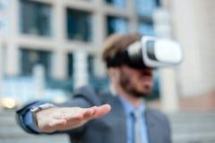 关闭一个年轻商人使用在办公楼前面的VR风镜,做手势 在他的手上的选择聚焦 库存图片
