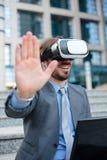 关闭一个年轻商人使用在办公楼前面的VR风镜 选择聚焦概念,在头的焦点 库存图片