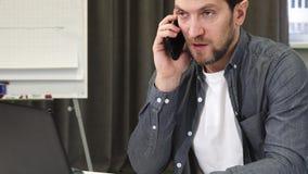 关闭一个成熟商人谈话在电话在办公室 免版税图库摄影